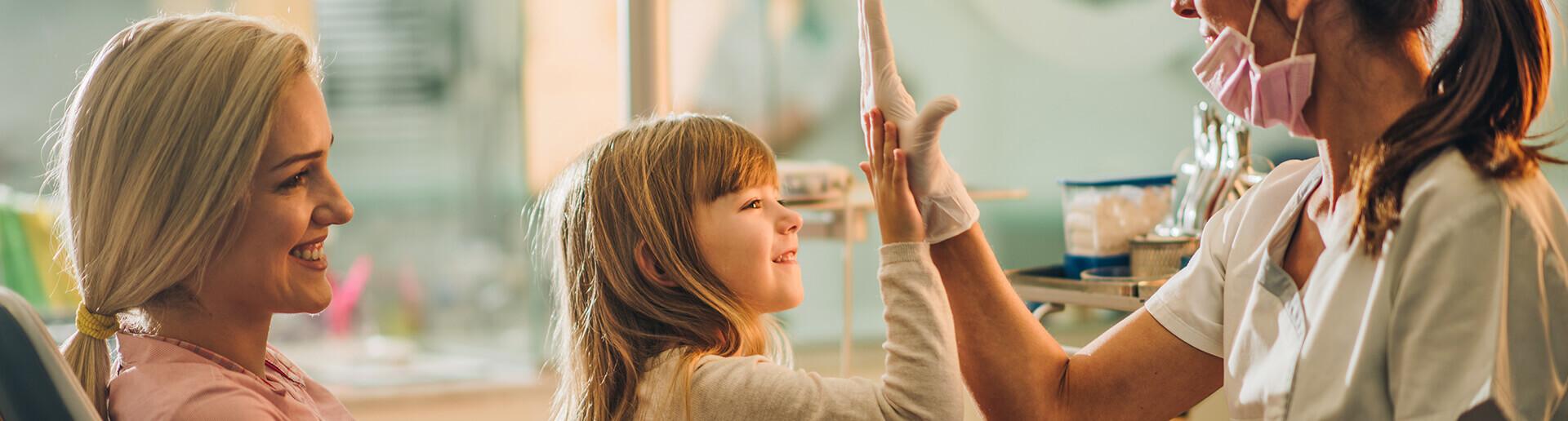 smiling mother holding her little girl as she high-fives her dentist