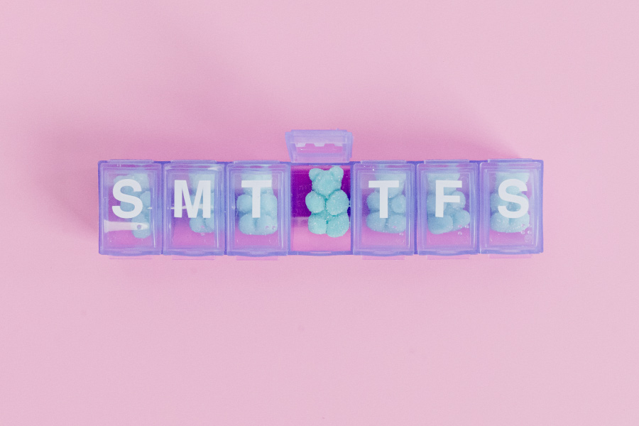 Blue gummy vitamins in a purple pill organizer for kids on a pink background