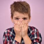 Boy with light brown hair in a plaid shirt covers his mouth because of bad breath in Columbus, OH